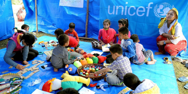 On 30 April, children play in a tent housing a UNICEF-supported child-friendly space in Tundikhel, a large grass-covered area and important landmark in Kathmanudu, the capital. A woman crouches nearby. A UNICEF counsellor was present at the space to talk with children about what they had endured. One of the tent's tarpaulins bears the UNICEF logo. A temporary camp has been set up in Tundikhel for internally displaced people.  By 30 April 2015 in Nepal, search, rescue and relief operations continued in the aftermath of the massive 7.8-magnitude earthquake that hit the country on 25 April. The quake's epicentre was 80 kilometres from Kathmandu, the capital. Over 5,500 people have been killed, and more than 11,100 others have been injured. Over 4.2 million people have been seriously affected, out of which an estimated 1.7 million – 40 per cent – are children below the age of 18 years. Residences, schools and vital infrastructure, including hospitals, have been severely damaged or destroyed, leaving thousands of children and families homeless, vulnerable to disease outbreaks and in urgent need of food, shelter, safe water and sanitation, and health support. Over 3 million people are estimated to be in need of food assistance, with 1.4 million needing priority assistance. Some 24,000 internally displaced people are being hosted in 13 camps in Kathmandu, the capital. Working with the Government and other partners, including fellow United Nations organizations, UNICEF is supporting water, sanitation and hygiene (WASH), health, nutrition, child protection, education and other interventions. In response to the disaster, UNICEF has provided tents, including for hospitals; tarpaulin sheeting; emergency medical kits; vaccines and related supplies; zinc and oral rehydration salts to prevent diarrhoeal disease outbreaks; water purification tablets; hygiene kits and buckets; and temporary learning spaces. Working with partners, psychosocial services have been initiated i