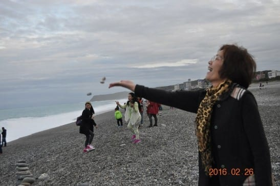 花蓮環保局副局長饒瑞玲親自將三顆石頭送回七星潭懷抱。〈圖片來源:花蓮環保局〉