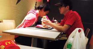 正在餵身障朋友吃漢堡的麥當勞店員何姓同學。(翻攝網路)