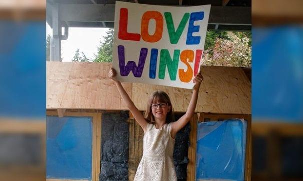 海莉高舉「愛贏了」牌子,認為主動付出愛相對也獲得幸福。(圖片摘自網路)