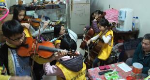 胡適國小弦樂團小志工們,跟著張其嵩牧師一同到受助戶家中拉提琴,演奏老歌給獨居長者聽。(圖片來源:基督教救助協會)