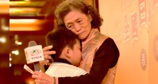 南投麗美阿嬤在台上分享人生,孫子哭著上台向阿嬤表示感謝,緊緊抱著阿嬤,堅強的阿嬤也因此紅了眼眶。(圖片來源:家扶基金會)