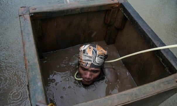 即便在下雨日,礦工們也忍著寒冷潛入視線不佳的水中。而且只靠著一支細管勉強呼吸。(圖片來源:asiancorrespondent.com)