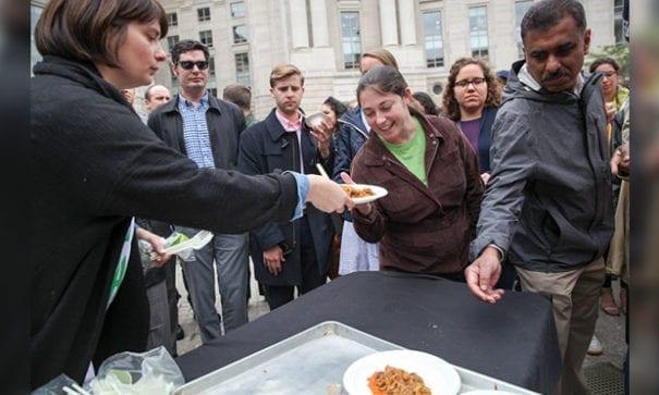 活動當天約6300人共襄盛舉,民眾從志工手中接過海鮮飯。(圖片來源:NPR)