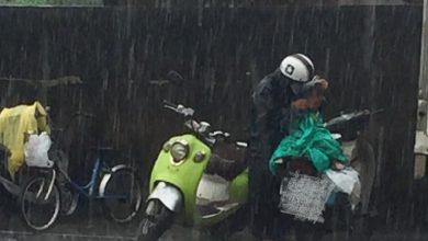 Photo of 阿公雙手護孫雨中排隊 等「別人吃剩的午餐」