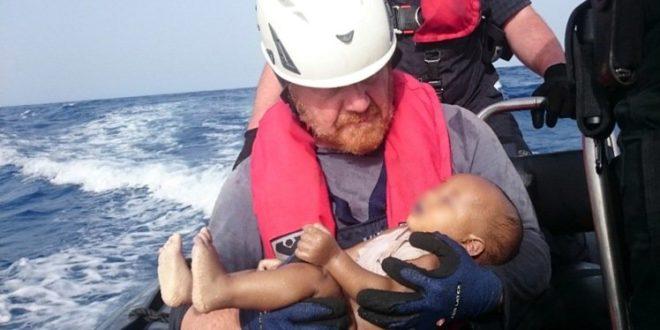 一位德國人道救援人員,將未滿一歲,即死於海上的難民小嬰兒,捧入懷中,令人不勝唏。(圖片來源/翻攝自網路)