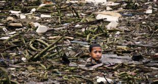 一名住在煙霧山周圍貧民窟裡的小孩,在充滿垃圾的河裡,找尋可賣錢的廢棄物品。(圖片來源/翻攝自網路)