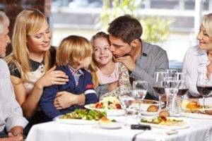 22649028 - father kissing daughter in restaurant while eating out with the family