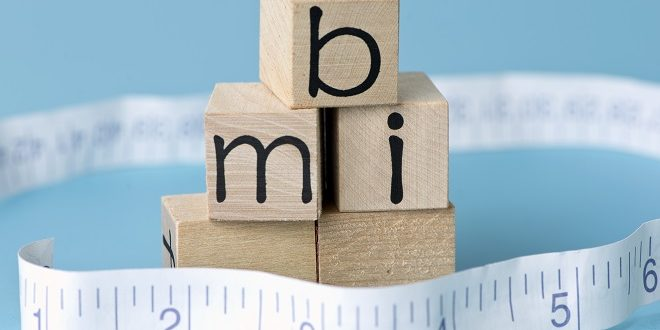 BMI body mass index letter blocks with tape measure.