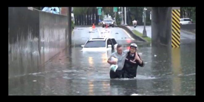 員警巢義信穿著警用雨衣,跳下約1公尺深的積水,救援受困涵洞的民眾。