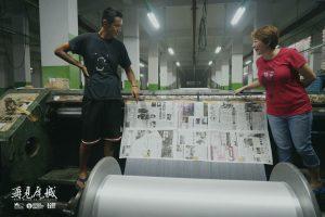 柯震東在異鄉看到有自己新聞的報紙相當興奮,與導演趙德胤的二嫂(右)分享喜悅。(圖片來源:岸上影像及前景娛樂提供)