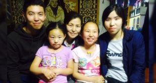 從蒙古來的布勒甘(左),來自單親家庭,經濟收入全靠母(中)賣糖果飲料支撐。他受到台灣認養者的幫助完成大學學業並來台讀研究所。(照片由家扶提供)