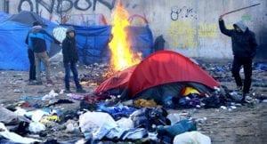 加萊難民營,生活環境髒亂、簡陋,難民們還得燒材火取暖。(圖片來源/翻攝自網路)