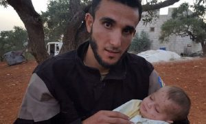 阿布開心的抱著當初被他救出的女嬰。(圖片來源/翻攝自網路 )