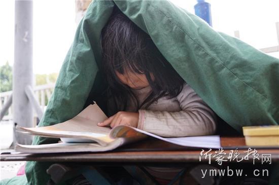 喜歡上學的紅紅表示,她不喜歡跟爸爸出來乞討,希望可以在家裡寫功課。(圖片來源:沂蒙晚報網)