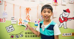 阿成一歲半跟著爸爸自助旅行,如今7歲的他已踏遍8個國家。阿成親手畫卡片掛上橘絲帶,為所有孩子平安祈福。(照片由兒盟提供)